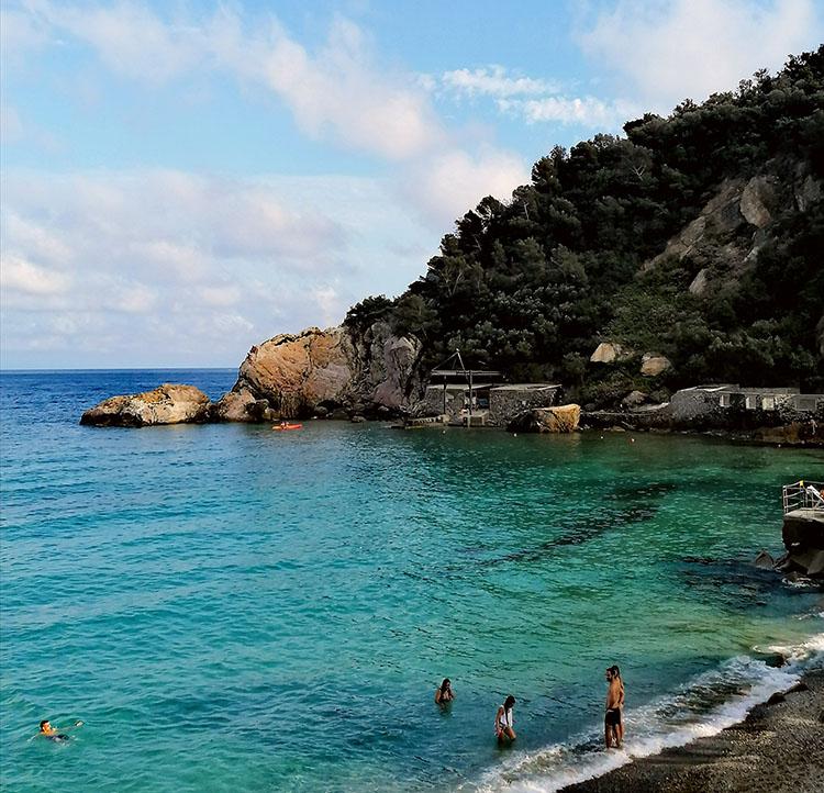 baia con mare azzurro e roccia